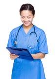 El doctor de la mujer escribe en el tablero Fotografía de archivo libre de regalías