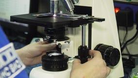 El doctor de la mujer mira en un microscopio almacen de metraje de vídeo