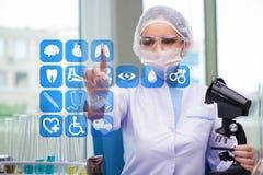 El doctor de la mujer que presiona los botones con los diversos iconos médicos Foto de archivo