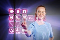 El doctor de la mujer que presiona los botones con los diversos iconos médicos Fotos de archivo libres de regalías