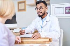 El doctor de Oriente Medio Consulting Female Patient imagenes de archivo