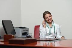 El doctor de sexo femenino acertado Talking On Cellphone en oficina fotografía de archivo libre de regalías