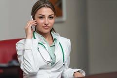 El doctor de sexo femenino acertado Talking On Cellphone en oficina imágenes de archivo libres de regalías
