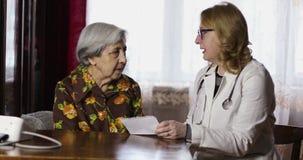 El doctor de sexo femenino alegre dice el tratamiento a una abuela con las arrugas profundas almacen de metraje de vídeo