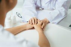 El doctor de sexo femenino amistoso da llevar a cabo la mano paciente que se sienta en Fotos de archivo libres de regalías