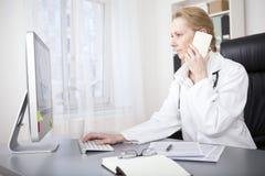 El doctor de sexo femenino Calling Phone While que usa el ordenador Imagen de archivo libre de regalías