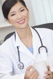 El doctor de sexo femenino chino Drinking Coffee o té de la mujer Foto de archivo libre de regalías