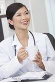 El doctor de sexo femenino chino Drinking Coffee o té de la mujer Imágenes de archivo libres de regalías