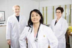 El doctor de sexo femenino confiado Smiling While Standing con los colegas imagenes de archivo