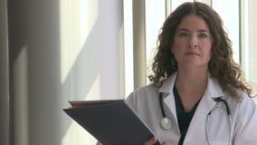 El doctor de sexo femenino da vuelta a la cámara y parece confiado (2 de 2)