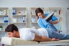 El doctor de sexo femenino del quiropráctico que da masajes al paciente masculino Fotografía de archivo libre de regalías