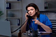 El doctor de sexo femenino envejecido que trabaja en el turno de noche foto de archivo