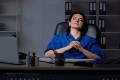 El doctor de sexo femenino envejecido que trabaja en el turno de noche fotografía de archivo