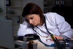 El doctor de sexo femenino envejecido que trabaja en el turno de noche imagen de archivo libre de regalías