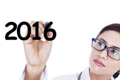 El doctor de sexo femenino escribe el número 2016 Foto de archivo