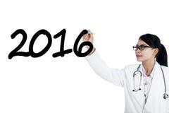 El doctor de sexo femenino escribe los números 2016 Imagen de archivo