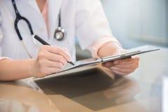 El doctor de sexo femenino está escribiendo algo en el tablero Fotos de archivo