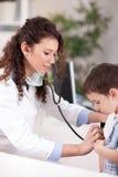 El doctor de sexo femenino examina al muchacho con el estetoscopio fotografía de archivo libre de regalías