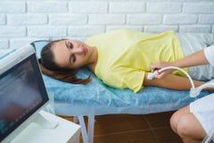 El doctor de sexo femenino examina la mano de las muchachas con ultrasonido en centro médico Fotos de archivo libres de regalías