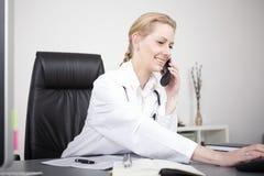 El doctor de sexo femenino feliz Calling Through Telephone Imagen de archivo