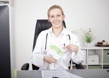 El doctor de sexo femenino feliz Holding una fan de 100 cuentas Imagenes de archivo