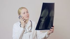 El doctor de sexo femenino habla en el teléfono y examina una imagen de la radiografía de la rodilla almacen de video