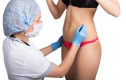 El doctor de sexo femenino hace la línea de puntos en el cuerpo femenino para la corrección de las celulitis Cirugía cosmética el Imagenes de archivo