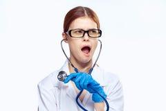 El doctor de sexo femenino hermoso joven en el fondo blanco sostiene un estetoscopio, retrato Fotos de archivo