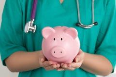 El doctor de sexo femenino Holding Piggy Bank Imagen de archivo