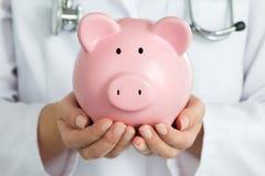 El doctor de sexo femenino Holding Piggy Bank Imágenes de archivo libres de regalías