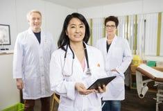 El doctor de sexo femenino Holding Tablet Computer mientras que se coloca con Collea imagen de archivo