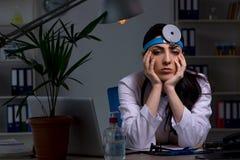 El doctor de sexo femenino joven que trabaja en el turno de noche imagen de archivo
