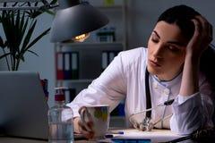 El doctor de sexo femenino joven que trabaja en el turno de noche fotografía de archivo