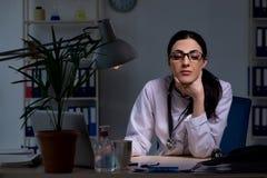 El doctor de sexo femenino joven que trabaja en el turno de noche imagen de archivo libre de regalías