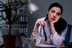 El doctor de sexo femenino joven que trabaja en el turno de noche foto de archivo