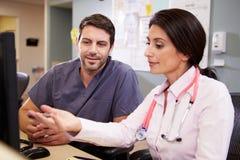 El doctor de sexo femenino With Male Nurse que trabaja en la estación de las enfermeras Fotografía de archivo libre de regalías