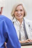 El doctor de sexo femenino mayor With Male Patient Imagenes de archivo