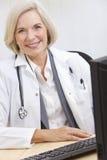 El doctor de sexo femenino mayor With Stethoscope en el escritorio Foto de archivo