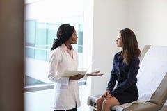 El doctor de sexo femenino Meeting With Patient en sitio del examen imagenes de archivo