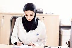 El doctor de sexo femenino musulmán llena los ficheros médicos imagen de archivo