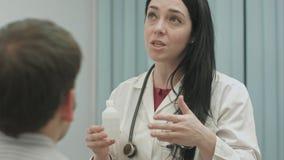 El doctor de sexo femenino que recomienda y habla del efecto de drogas al paciente imagen de archivo