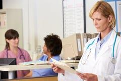 El doctor de sexo femenino Reading Patient Notes At cuida la estación Imagenes de archivo