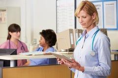 El doctor de sexo femenino Reading Patient Notes At cuida la estación Imagen de archivo