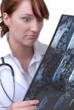 El doctor de sexo femenino Reading una radiografía fotos de archivo libres de regalías