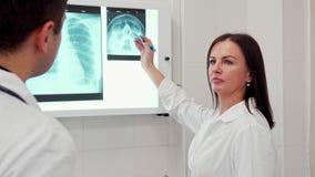 El doctor de sexo femenino señala el lápiz en la radiografía de la cabeza humana fotos de archivo