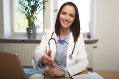 El doctor de sexo femenino se está sentando en su escritorio y saluda a un paciente Fotos de archivo libres de regalías