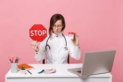 El doctor de sexo femenino se sienta en el trabajo de escritorio en el ordenador con las píldoras médicas del control del documen imagen de archivo