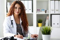 El doctor de sexo femenino sonriente hermoso escribe la prescripción Fotografía de archivo