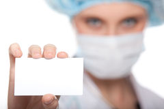 El doctor de sexo femenino sostiene una tarjeta en blanco Imágenes de archivo libres de regalías