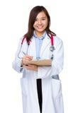 El doctor de sexo femenino toma la nota sobre el tablero fotos de archivo libres de regalías